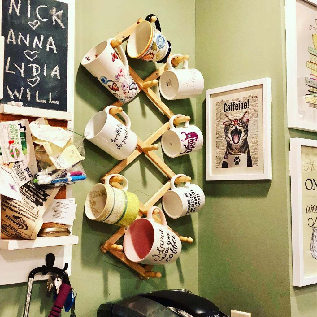 coffee cups hanging on mug wall rack with green paint in the background