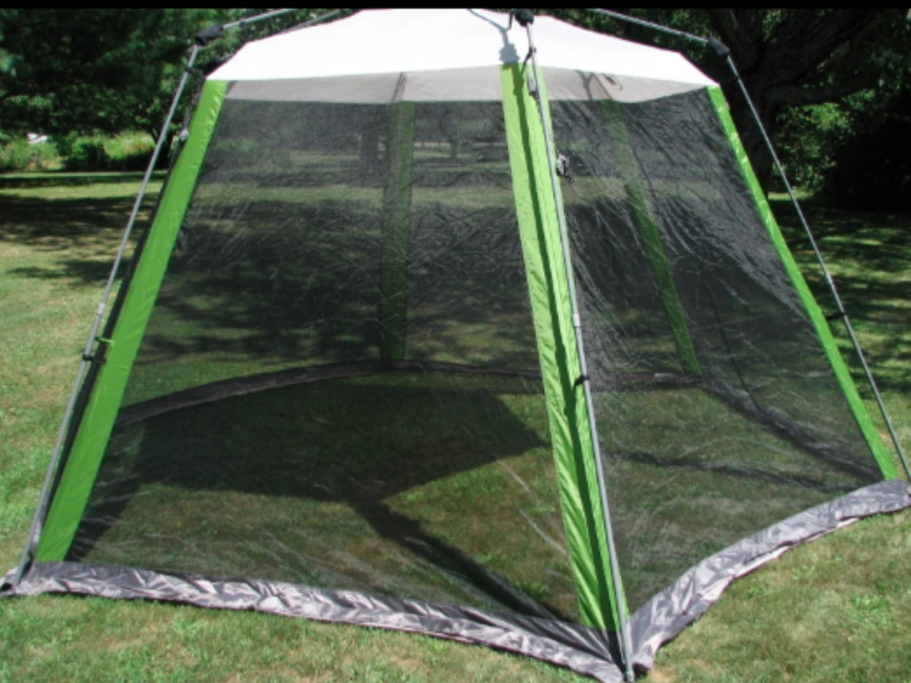 green and white coleman screened in tent outdoors