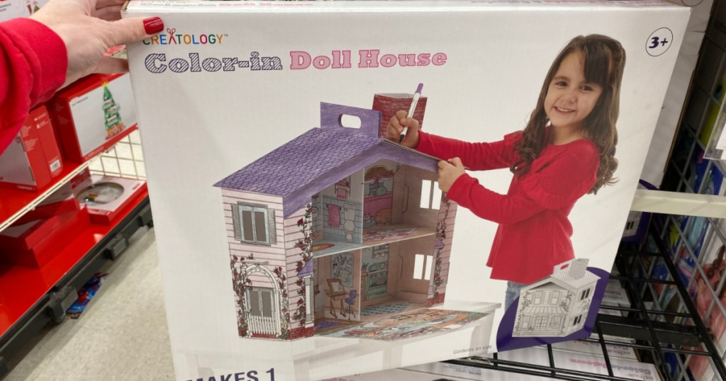 hand holding creatology color-in doll house