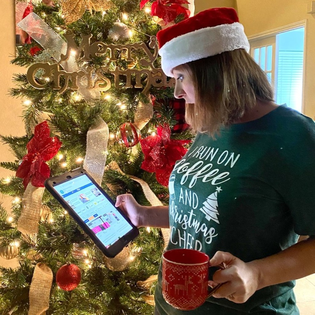 woman looking at tablet in front of Christmas tree