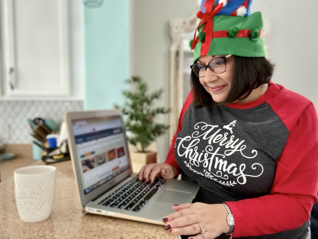 woman dressed for Christmas looking at laptop