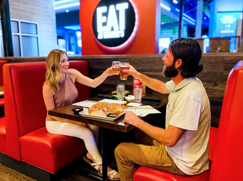 couple holding up drinks for a cheers in dave and busters booth