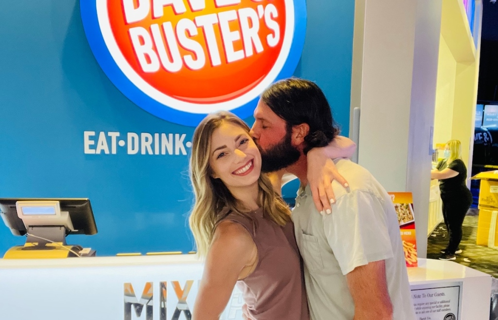 man kissing womans cheek with dave and busters sign in background