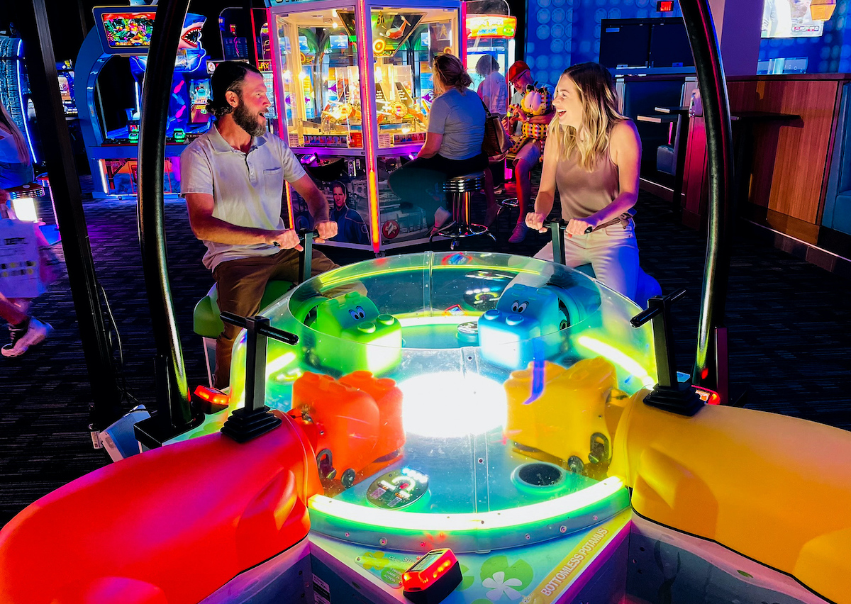 couple sitting on hungry hungry hippo game at dave and busters