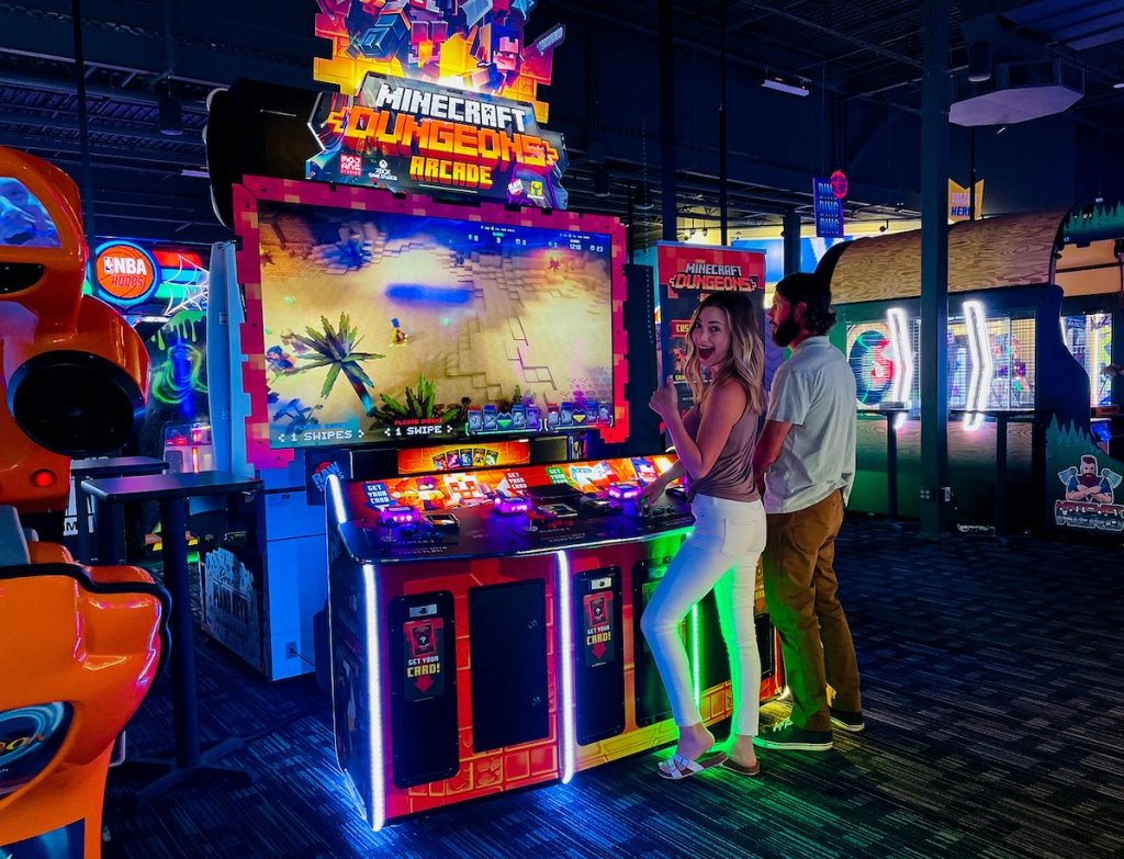 couple standing at minecraft video game at dave and busters