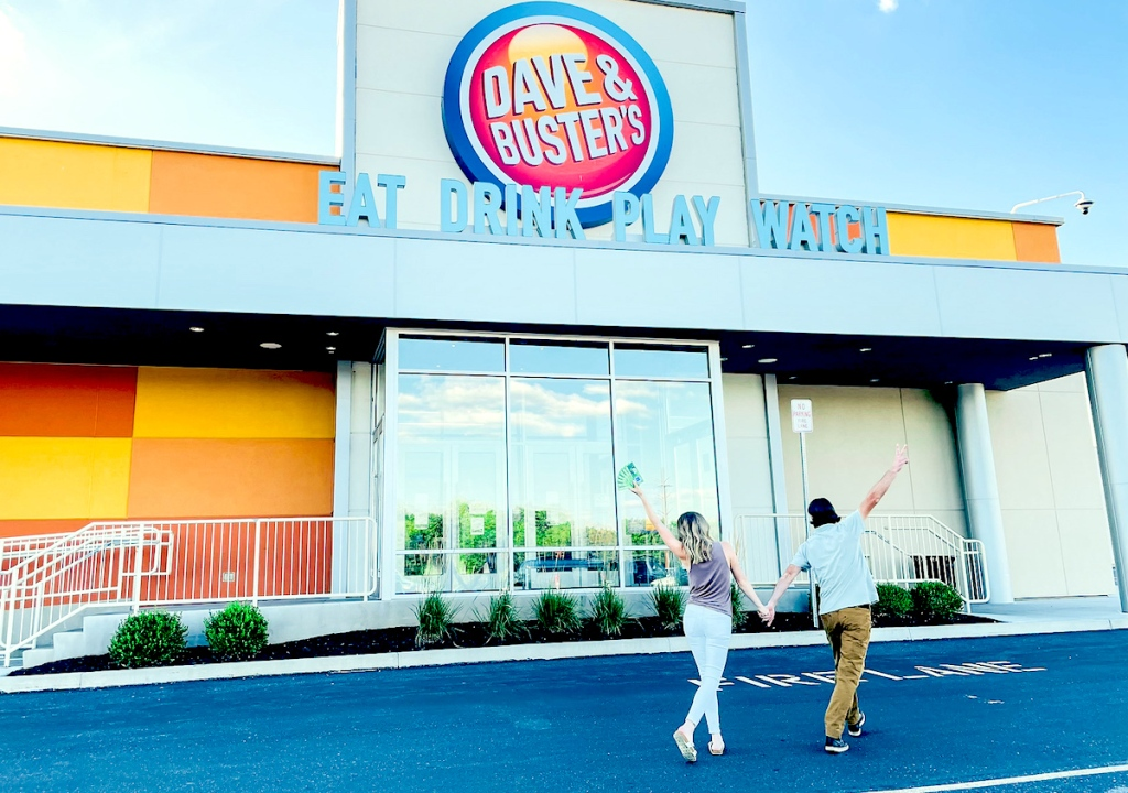 couple walking into dave and busters storefront