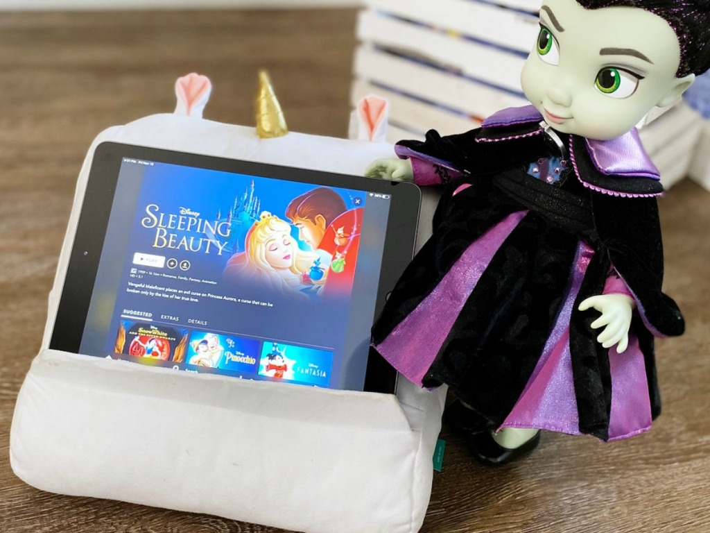 doll next to tablet with unicorn cover on it