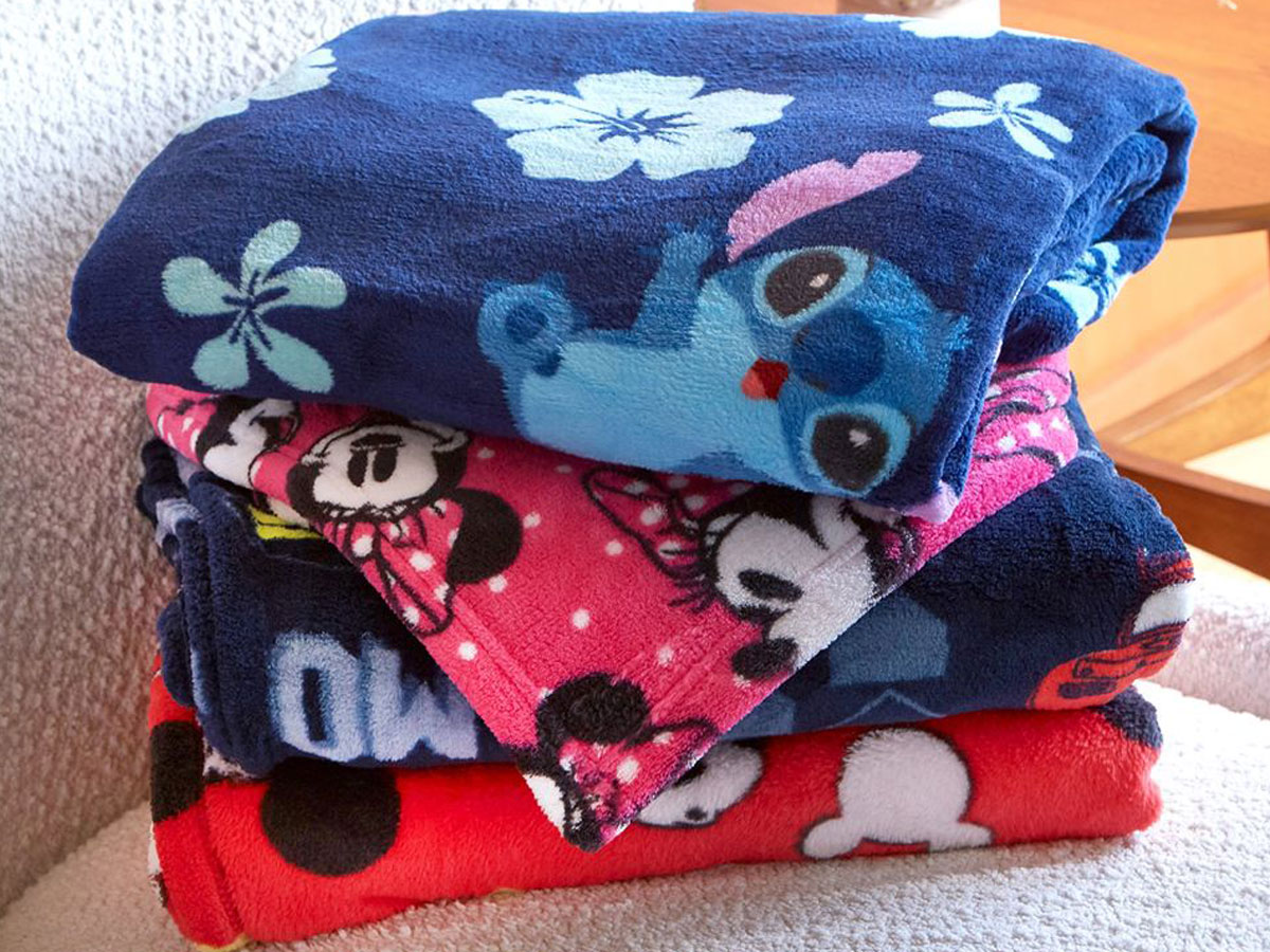disney blankets stacked on a chair