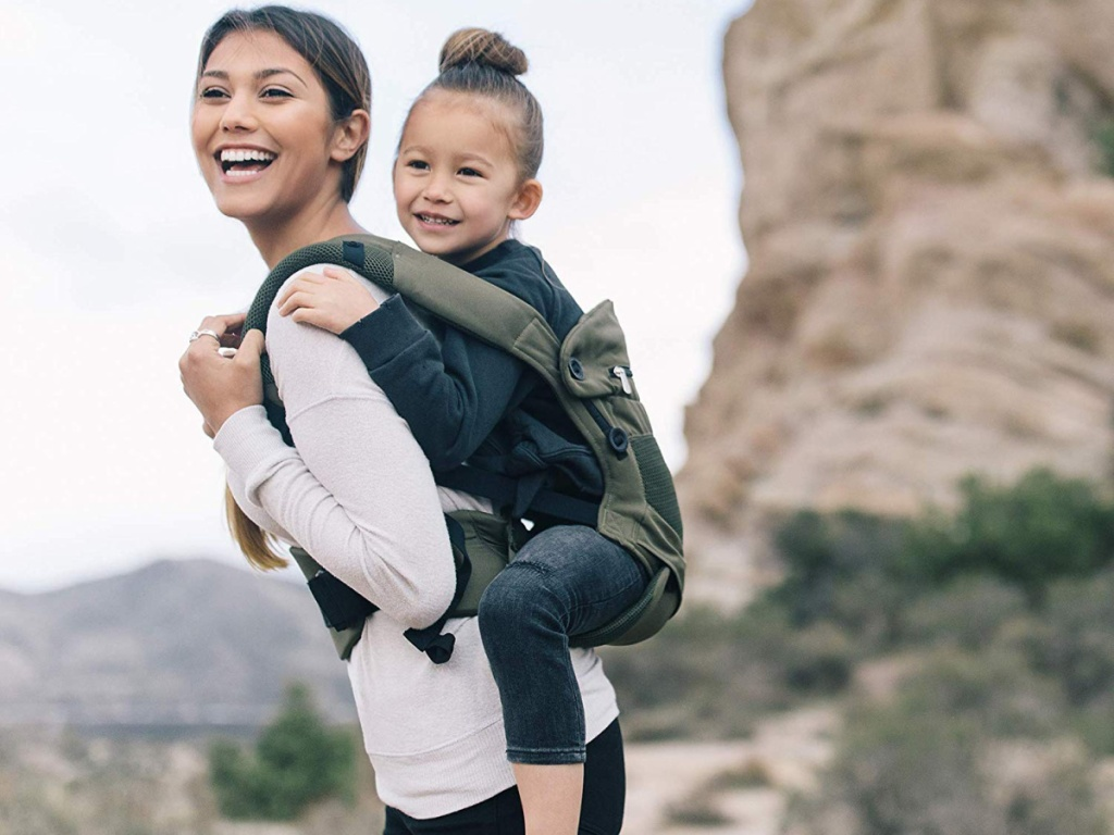 woman carrying daughter in green baby carrier with mountains in background