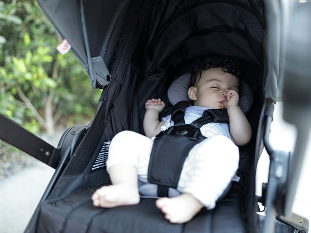baby in stroller laying on gray stroller pad