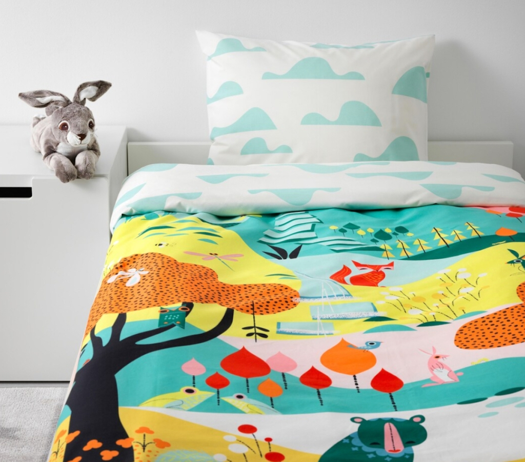 white bedroom with colorful fairytale themed bedding on bed