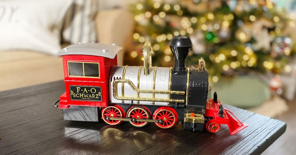 FAO Schwarz train sitting on a table christmas tree in the background