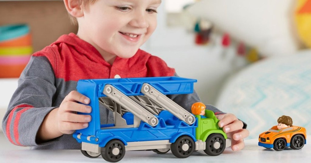 little boy playing with fisher price little people carrier truck