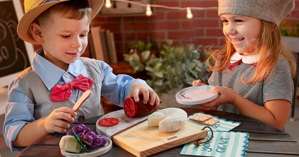 2 kids playing with a Fisher-Price Charcuterie Board