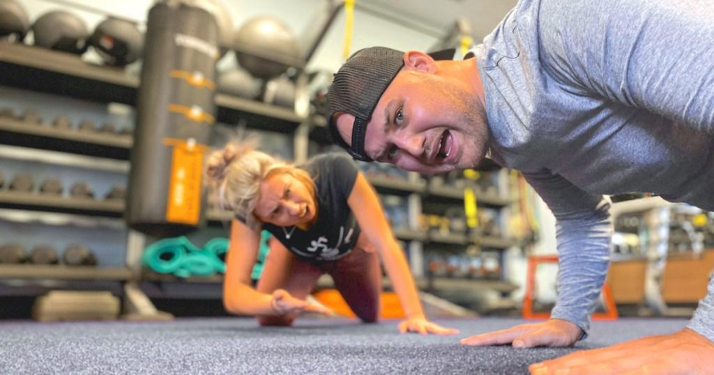 man and woman doing push ups on gym floor