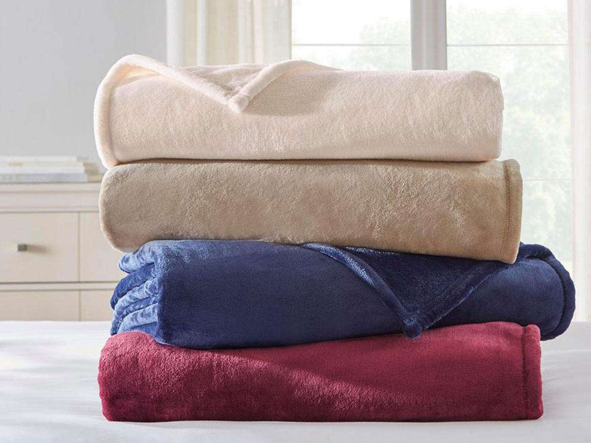home depot plush fleece blankets stacked on top of each other in four colors