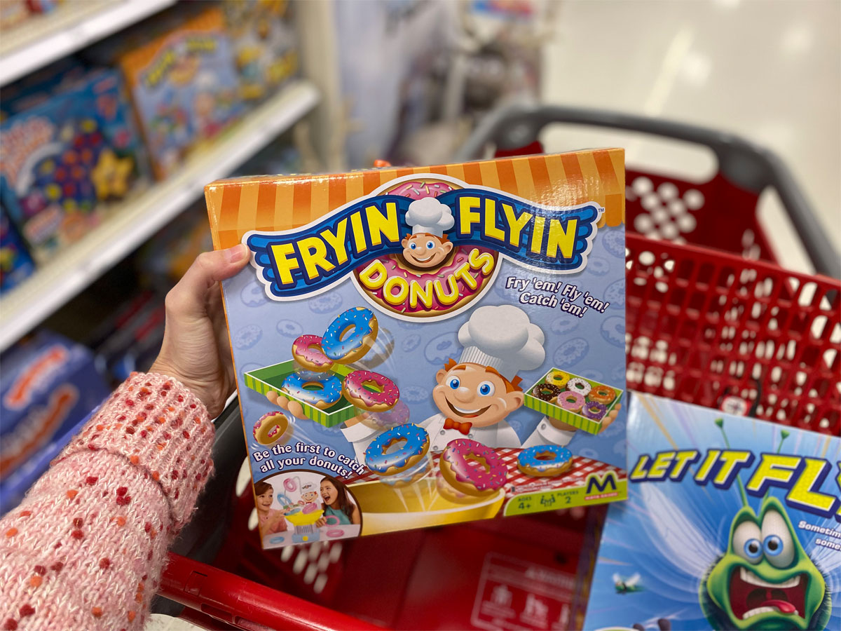 hand holding a maya game of frying flying donuts in a target shopping cart
