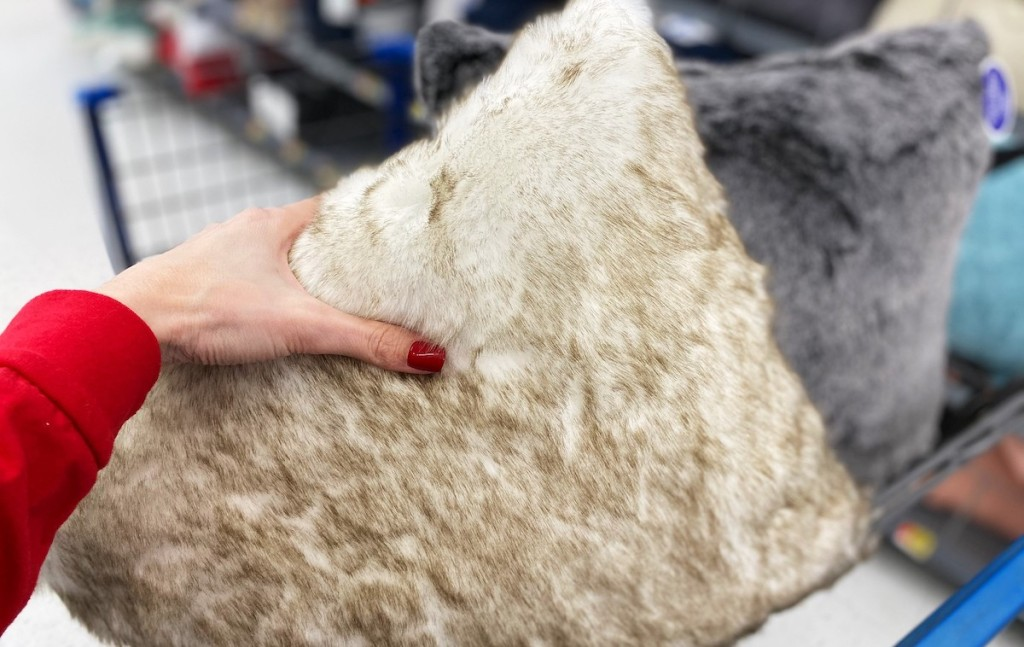 hand holding a beige and white fur throw pillow