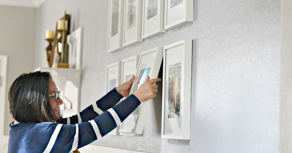 woman holding white picture frame on gallery wall