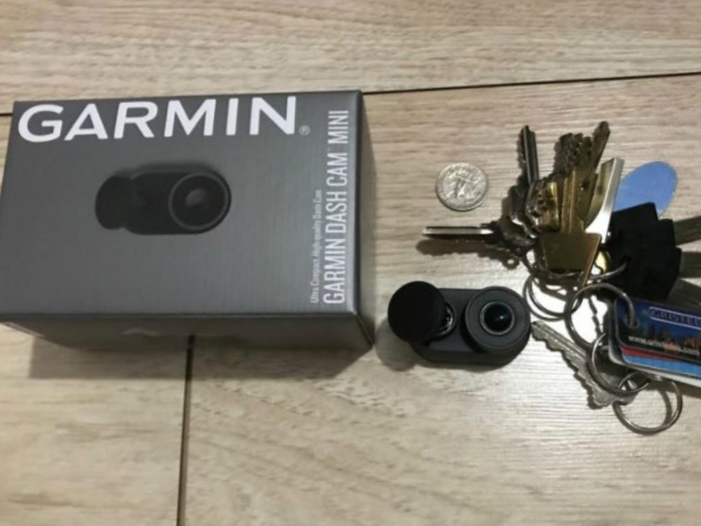 box with small camera on table with keys