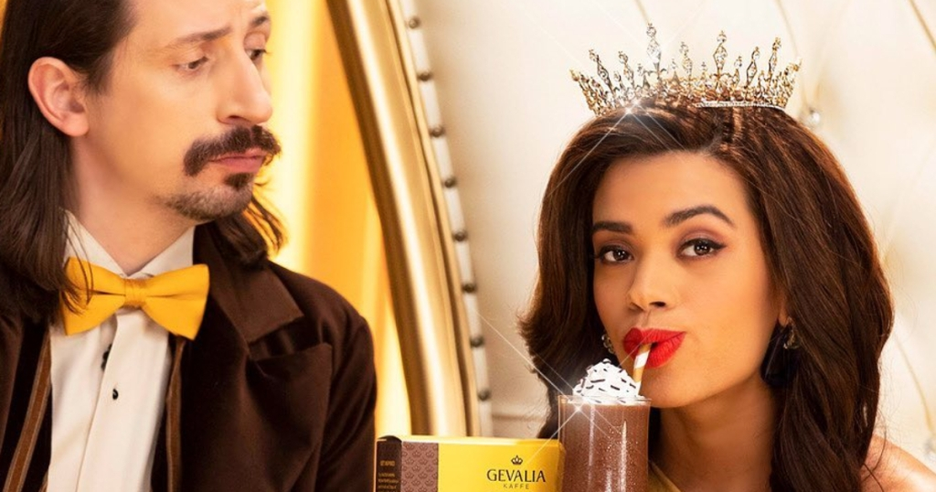 woman wearing a crown sipping iced coffee while a man in a bowtie watches
