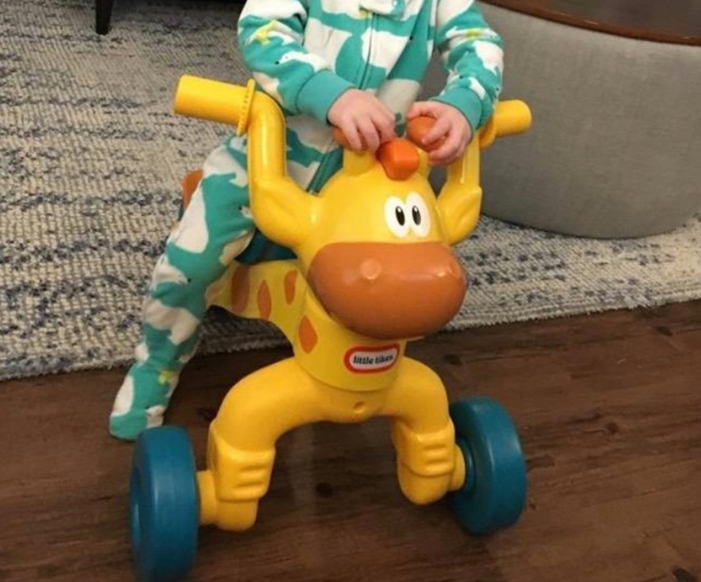 popular kids toys christmas 2020 yellow giraffe ride on toy with toddler sitting in pajamas on top