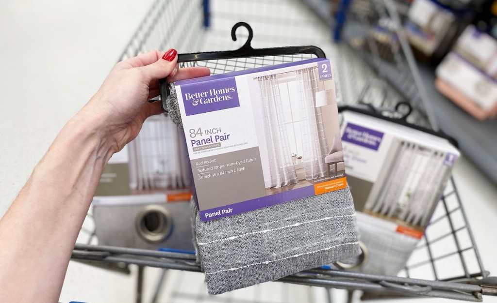 hand holding a package of gray curtains