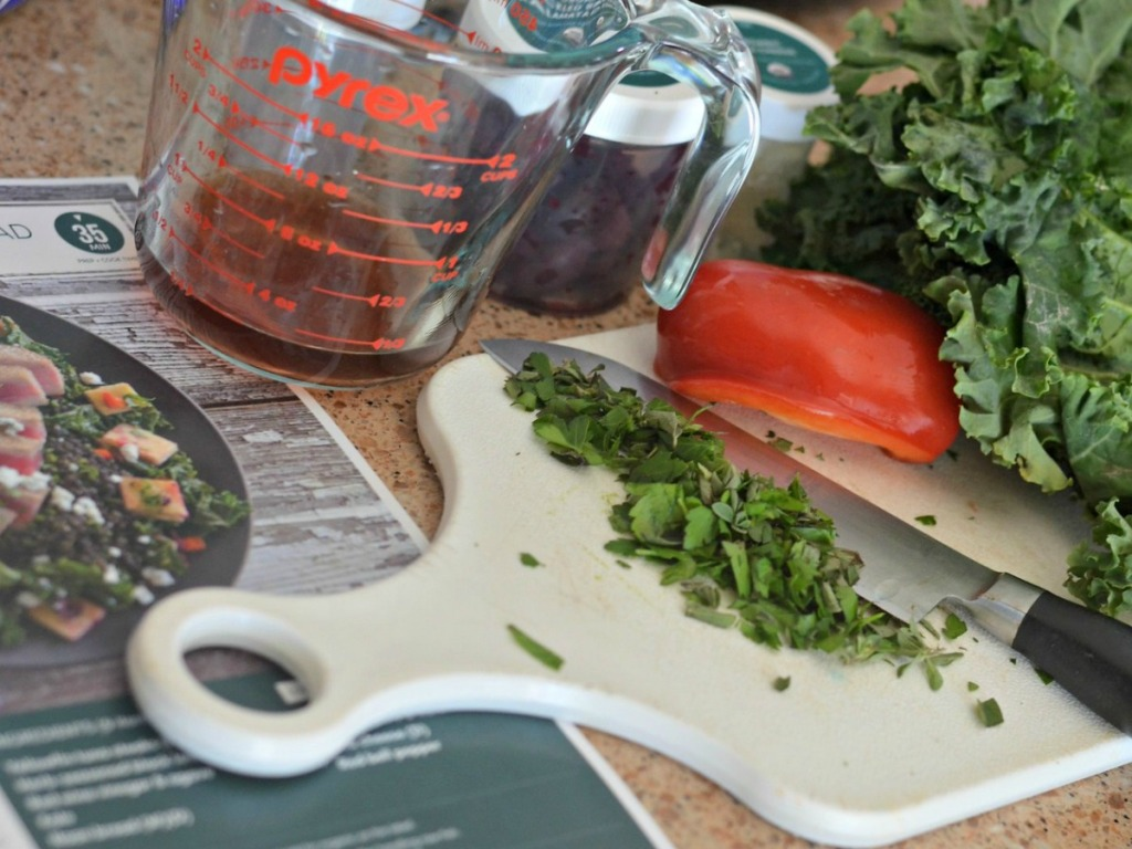 cutting board with chopped kale, red pepper and misc ingredients on counter