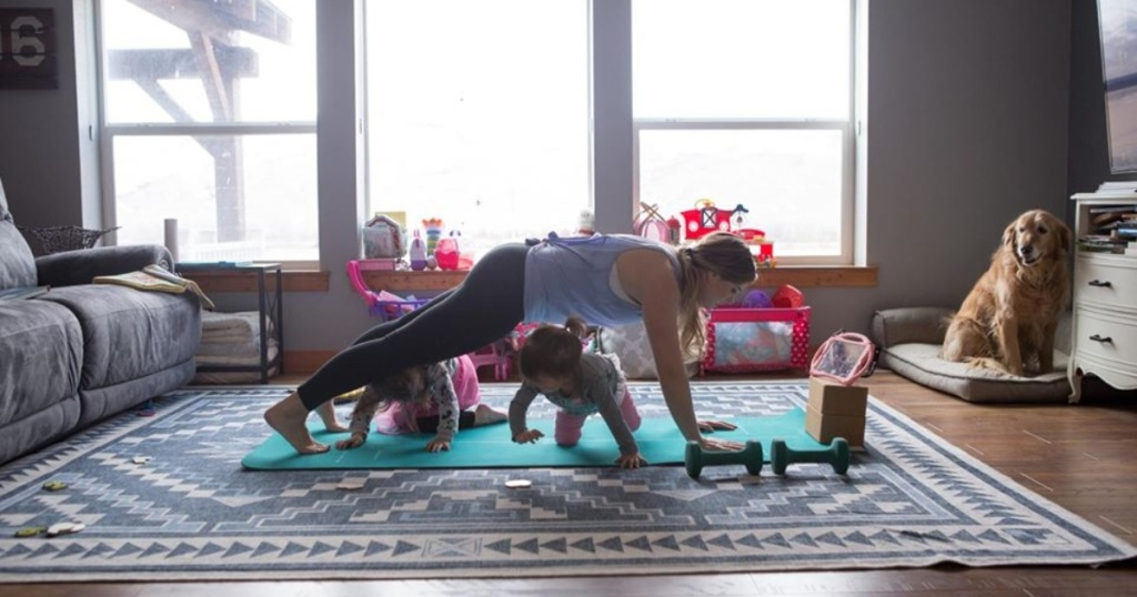 woman working out at home with 2 kids