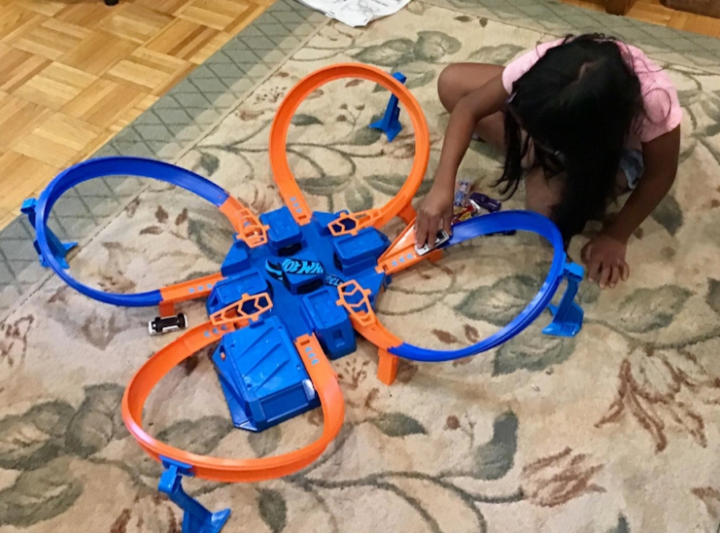 blue and orange hot wheels track on carpet rug