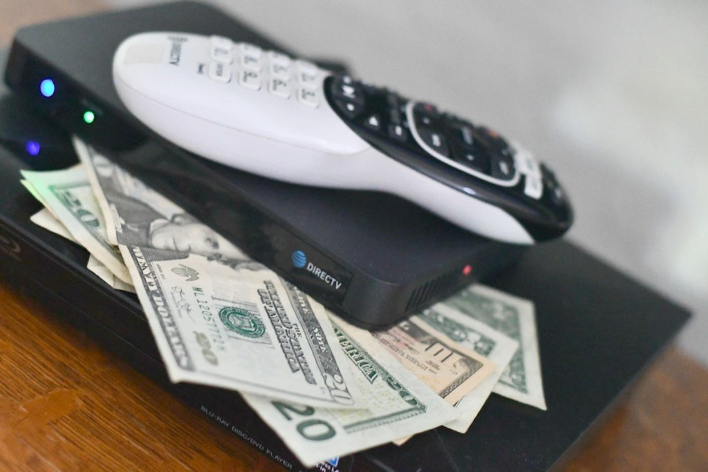 direct tv remote on top of cash money