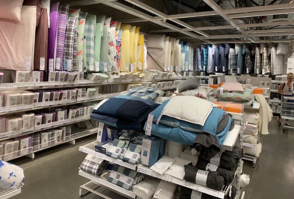 rows of various colored bedding hanging from store shelves