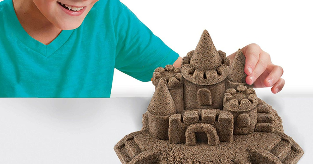 child playing with sand formed into castle