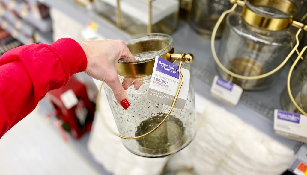 hand holding clear glass and brass lantern