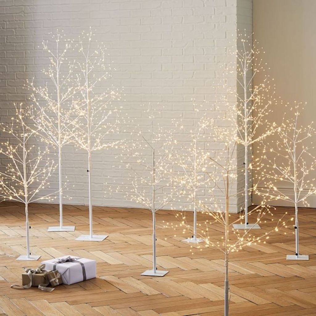 white led trees with one present in room