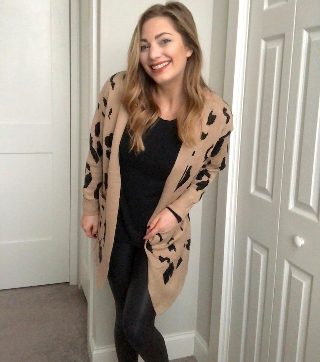 woman smiling wearing beige and black leopard cardigan and black leggings and shirt