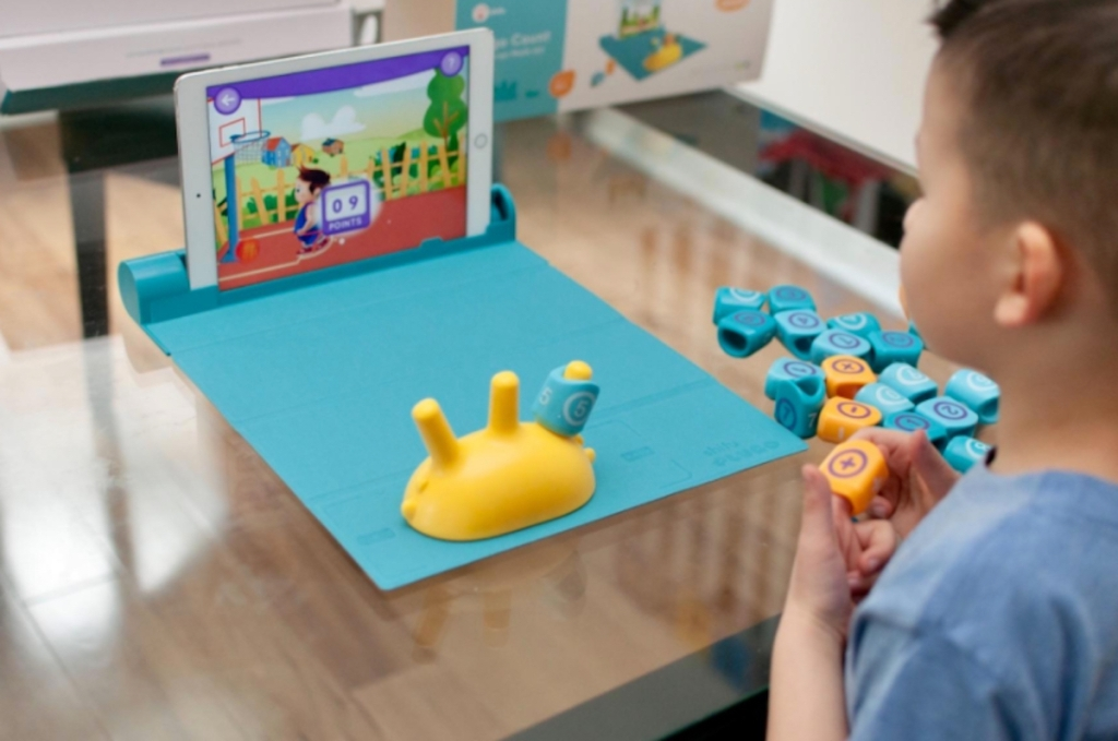 boy playing math game on blue board with ipad