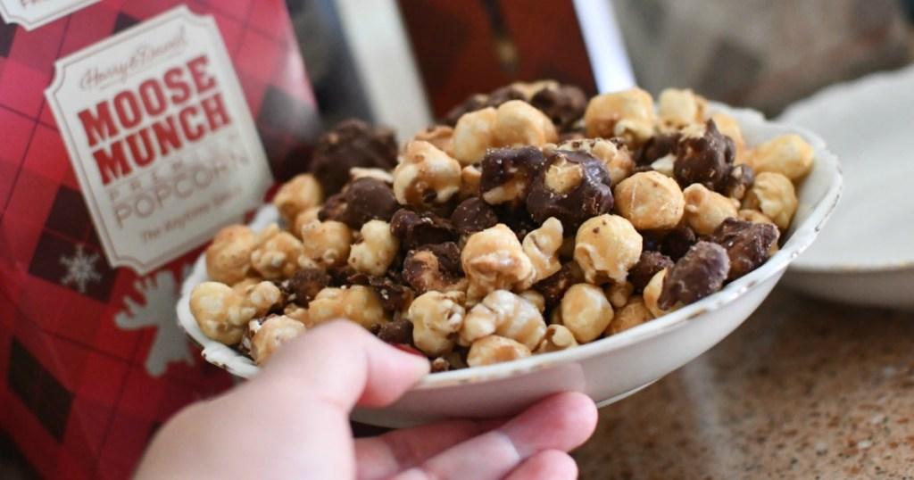 holding Moose Munch popcorn in bowl