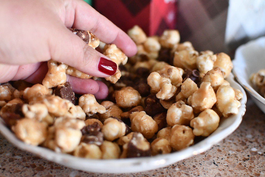 picking up Moose Munch popcorn from bowl