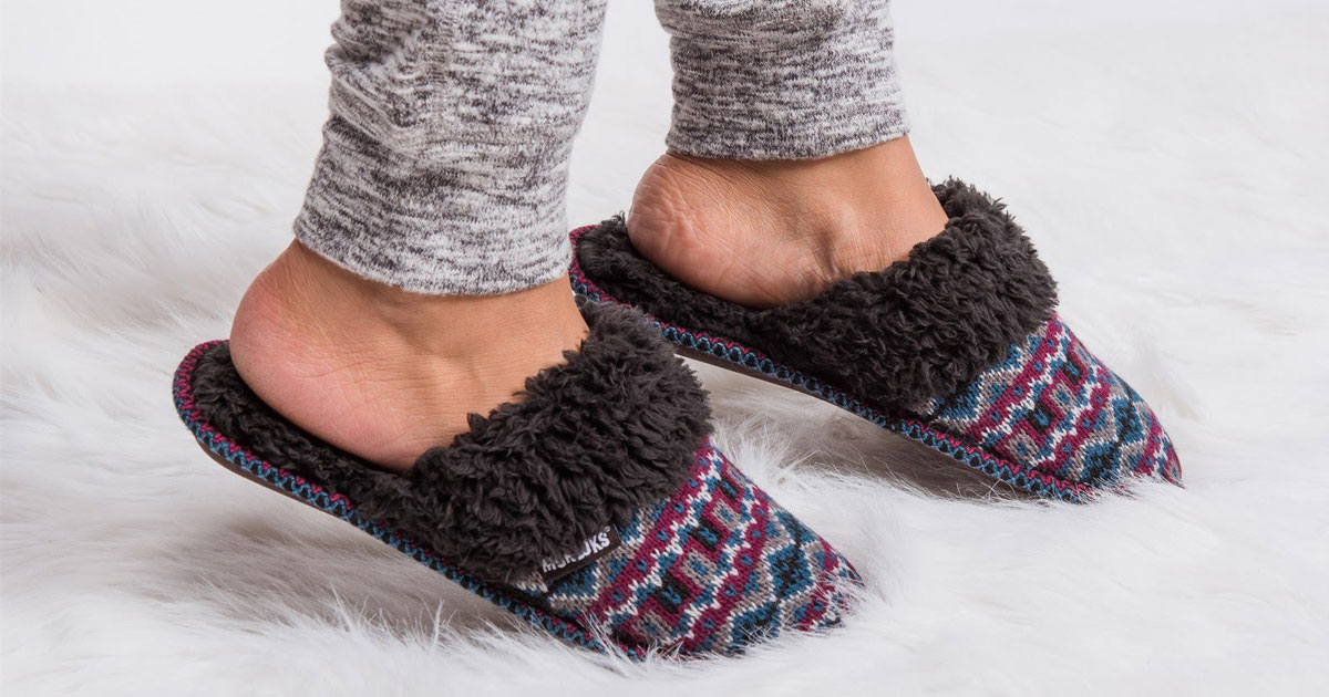 Muk Luks slippers on a fur rug