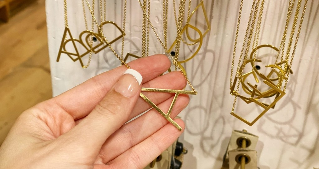 hand holding a gold A necklace with others hanging on store shelf