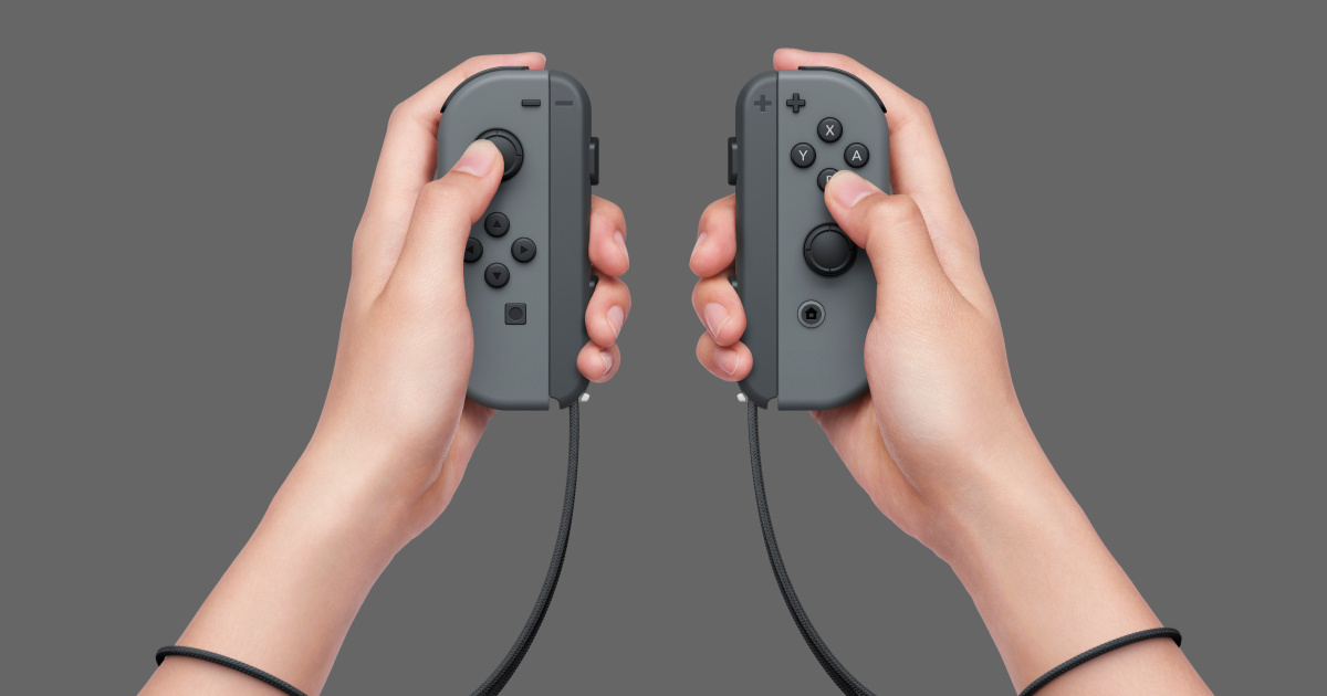 hands holding nintendo controllers