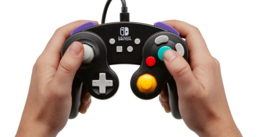 hands holding up black nintendo switch controller