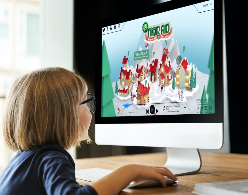 little girl sitting in front of the norad santa tracker virtual north pole on computer screen