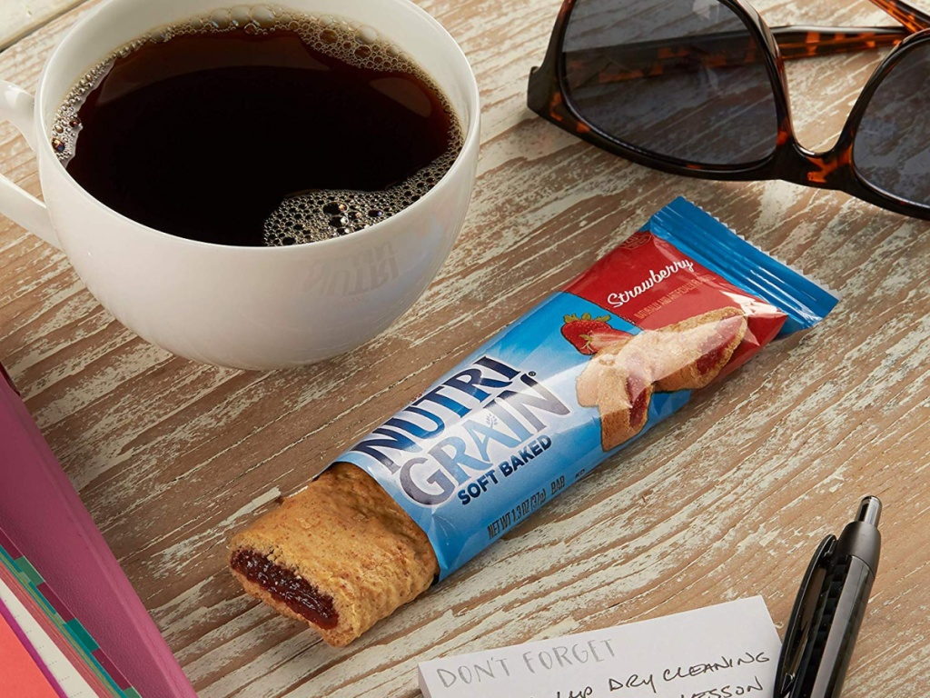 nutri-grain bar on table with coffee cup and sunglasses beside it