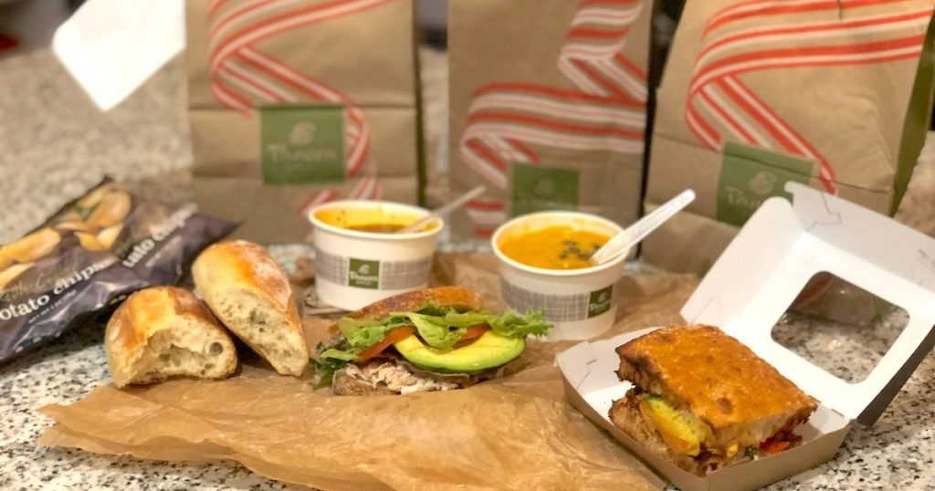 various sandwiches and soup with panera bags sitting on kitchen counter