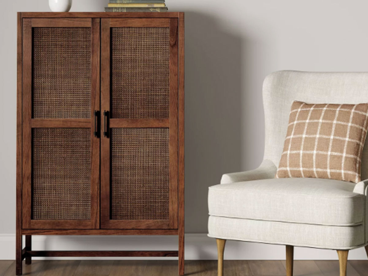 Threshold Warwick Wood & Rattan Library Cabinet in a room by a chair
