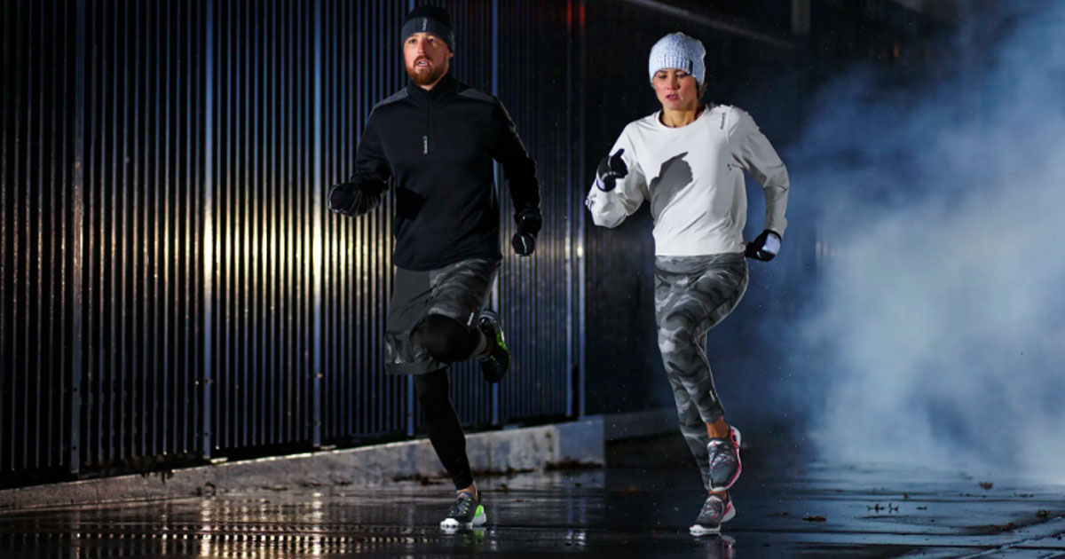 man and woman running in the darkness of night with brand name running shoes