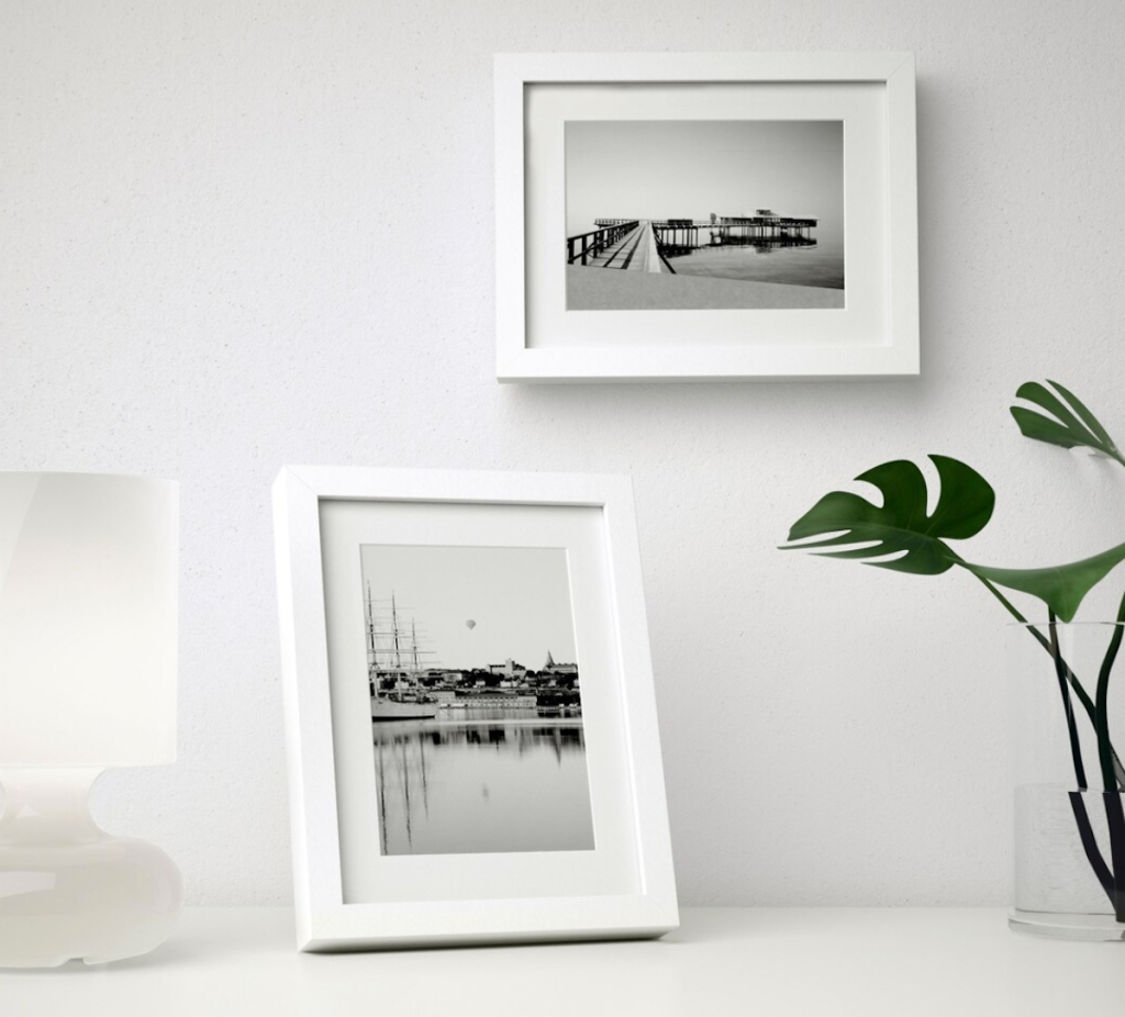 two white picture frames on white desk and wall
