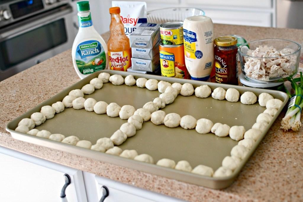 sheet pan with pizza dough balls and 4 dips